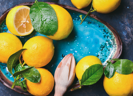 Close-up of freshly picked lemons with leaves in bright blue ceramic plate, top view, copy space, horizontal composition Stock Photo