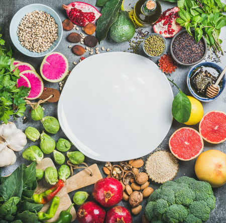 Clean eating concept over grey background with white plate in center, top view, copy space. Vegetables, fruit, seeds, cereals, beans, spices, superfoods, herbs for vegan, raw diet and gluten free diet Stock Photo
