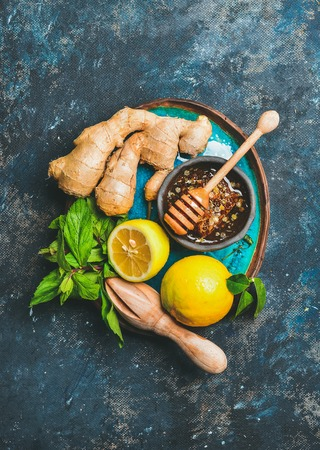 pounder: Ingredients for making natural hot drink in blue ceramic plate over dark blue shabby background, top view. Orange, fresh mint, lemon, ginger, honey. Clean eating, healthy lifestyle, dieting concept Stock Photo