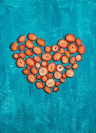 Pieces of fresh red strawberry placed in shape of heart over bright blue painted wooden background, top view, copy space. Love concept. Greeting card for Saint Valentine s or Lovers Day
