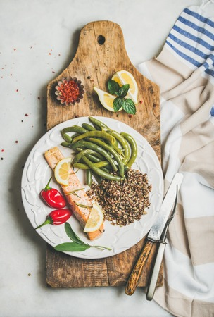 Healthy protein rich dinner plate. Oven roasted salmon fillet with multicolored quinoa, chilli pepper and poached green beans on rustic wooden board over grey background, top view. Diet food concept