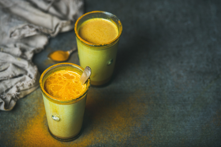Golden milk with turmeric powder in glasses over dark grunge background, copy space. Health and energy boosting, flu remedy, natural cold fighting drink. Clean eating, detox, weight loss concept Stock Photo