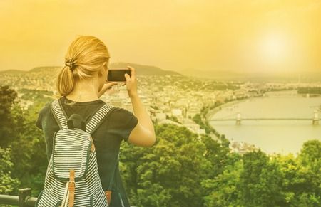 Young blond woman tourist making photoes of Danube river and Budapest from hill with smartphone, rear view, Hungary