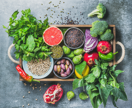 Vegetables, fruit, seeds, cereals, beans, spices, superfoods, herbs, condiment in wooden box for vegan, gluten free, allergy-friendly, clean eating or raw diet. Grey concrete background and top view Stock Photo