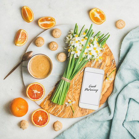 Cup of morning coffee, cookies, red oranges, bucket of spring flowers and mobile phone with text Good morning on board over light grey marble background, top view. Morning greeting card concept Stock Photo