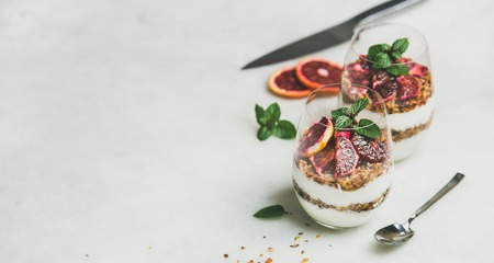 Healthy breakfast. Greek yogurt, granola, blood orange layered parfait in glasses with mint leaves over grey marble background, copy space. Clean eating, weight loss, detox, dieting food concept Stock Photo