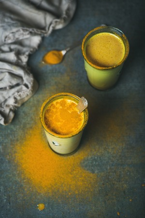 warming therapy: Golden milk with turmeric powder in glasses over dark grunge background, copy space. Health or energy boosting, flu remedy, natural cold fighting drink. Clean eating, dieting, weight loss concept