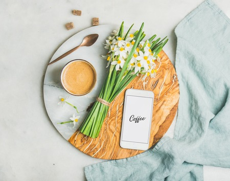 Cup of morning coffee, bucket of spring flowers and mobile phone with text Coffee on serving board over light grey marble background, top view. Morning greeting card concept