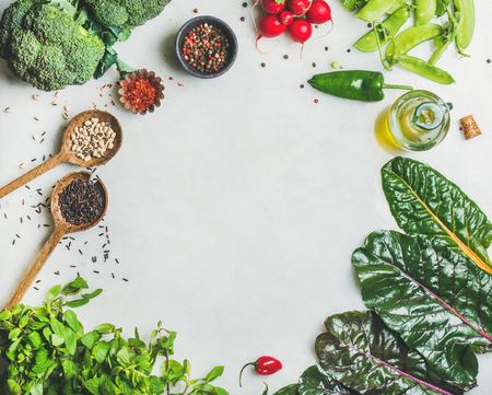 Fresh raw greens, vegetables, olive oil and grains over light grey marble kitchen countertop, top view, copy space. Healthy, clean eating, vegan, vegetarian, detox, dieting food concept Stock Photo