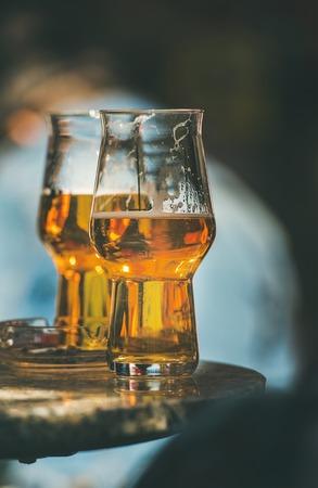 Dos vasos de cerveza sobre una mesa en un café callejero, enfoque selectivo, composición vertical Foto de archivo - 75304935