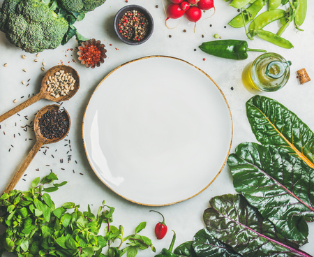countertop: Fresh raw greens, vegetables and grains over light grey marble kitchen countertop, wtite ceramic plate in center, top view, copy space. Healthy, clean eating, vegan, detox, dieting food concept