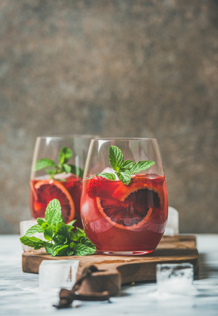 Blood orange and strawberry summer Sangria. Fruit refreshing rose wine cocktails in glasses with ice and mint, dark background, vertical composition, copy space