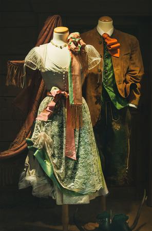 Oostenrijkse volkskostuums of -kleding voor mannen en vrouwen. Traditionele Tracht. Vrouwelijke jurk Dirndl en heren Lederhosen korte rijbroek gemaakt van leer, en colbert