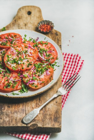 Fresh heirloom tomato, parsley and onion salad in white plate on serving wooden board over light grey marble background, selective focus. Clean eating, vegan, vegetarian, healthy, dieting food concept