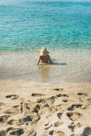 Beautiful slim senior woman tourist in bikini and hat lying on sand enjoying clear sea waters at Meditteranean resort of Turkey in Alanya, Kleopatra beach, rear view Stock Photo