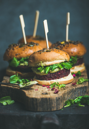 Healthy vegan burger with beetroot and quinoa patty, arugula, avocado sauce and wholegrain buns on rustic wooden board over dark background, selective focus. Clean eating, dieting, vegan food concept