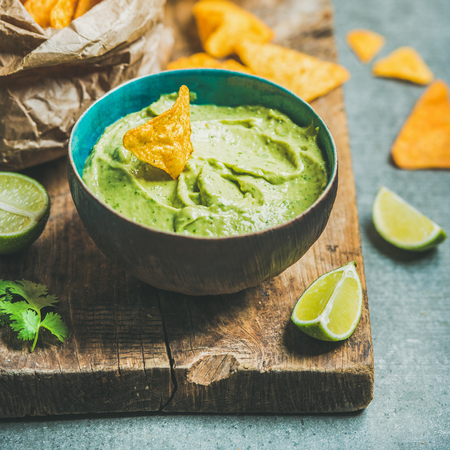 Fresh guacamole sauce in blue bowl, mexican corn chips, glass of wheat beer on rustic wooden serving board over grey concrete table background, selective focus, square crop