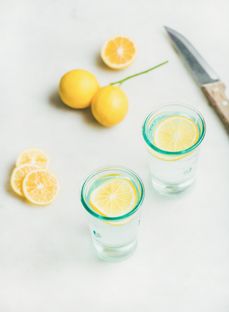 Morning detox lemon water in glasses and fresh lemons over light grey marble background, selective focus, vertical composition. Clean eating, weight loss, healthy, detox, dieting concept
