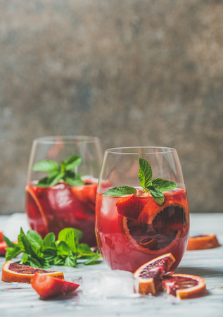 Blood orange and strawberry summer Sangria. Fruit refreshing rose wine cocktails in glasses with ice and mint leaves, dark background, vertical composition, copy space Stock Photo