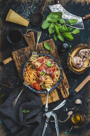 plywood: Italian style pasta dinner. Spaghetti with tomato and basil in plate on wooden board and ingredients for cooking pasta over dark blue plywood background, top view, vertical composition