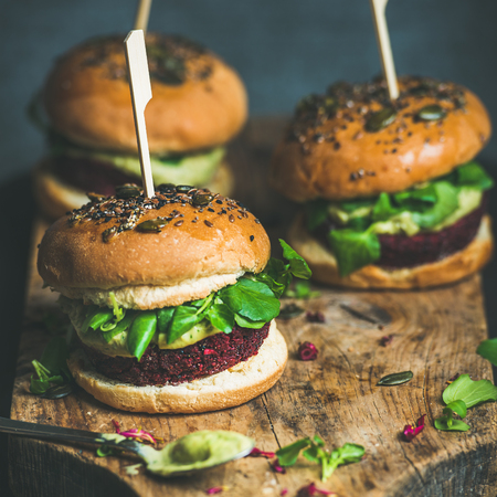 Healthy vegan burgers with beetroot and quinoa patty, arugula, avocado sauce, wholegrain bun on rustic wooden board over dark background, selective focus, copy space, square crop. Vegan food concept