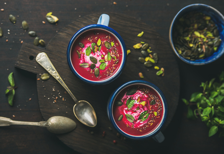 Spring detox beetroot soup with mint, pistachio, chia, flax and pumpkin seeds in blue enamel mugs over dark wooden background, top view. Clean eating, healthy, vegetarian, dieting, weight loss concept