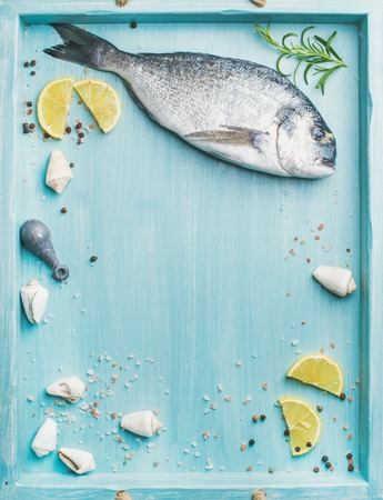 Fresh Sea bream or dorado raw uncooked fish with seasoning and lemon slices over turquoise blue tray background, top view, copy space Stock Photo
