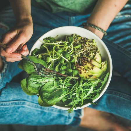 Green vegan breakfast meal in bowl with spinach, arugula, avocado, seeds and sprouts. Girl in jeans holding fork with knees and hands visible, top view, square crop. Clean eating, dieting food concept
