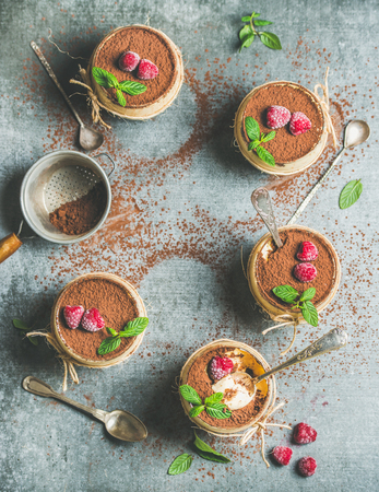 Homemade Italian dessert Tiramisu served in individual glasses with fresh mint leaves, raspberries and cocoa powder in sieve over grey concrete background, top view, copy space, vertical composition