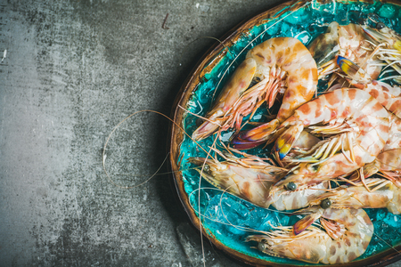 Raw uncooked tiger prawns on chipped ice in turquoise blue ceramic tray over grey concrete background, top view, copy space, horizontal composition. Fresh seafood Stock Photo