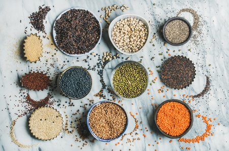 Variety of raw uncooked grains, beans, cereals in bowls, cups and baking molds for healthy cooking over marble background, top view. Clean eating, healthy, detox, vegan, vegetarian food concept