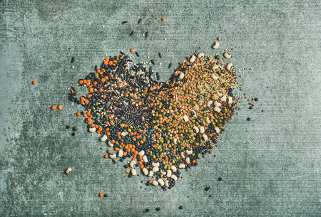 Various raw uncooked grains, beans, cereals in shape of heart over grey concrete background, top view, horizontal composition. Clean eating, healthy, detox, vegan, vegetarian food concept Фото со стока - 79380908