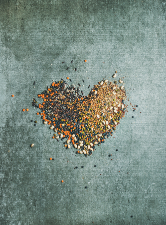 Variety of raw uncooked grains, beans, cereals in shape of heart over grey concrete background, top view. Clean eating, healthy, detox, vegan, vegetarian food concept Stock Photo