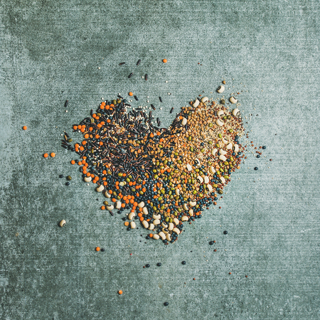 Various raw uncooked grains, beans, cereals in shape of heart over grey concrete background, top view, square crop. Clean eating, healthy, detox, vegan, vegetarian food concept Stock Photo