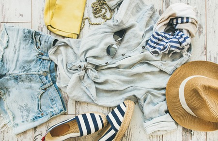 Summer outfit flatlay. Pastel summer womens clothes, parquet background, top view. Blue denim shorts, linen shirt, straw hat, yellow bag, sunglasses, blue and white striped neckerchief, espadrillas