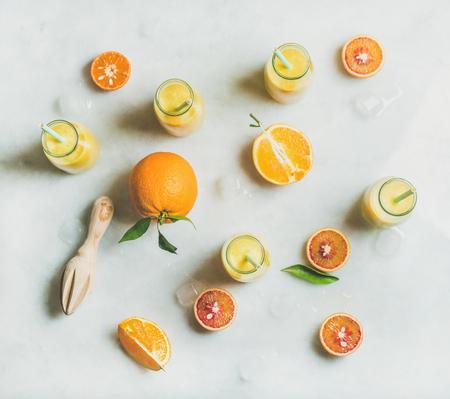 柑橘系の果物、生姜、氷光大理石テーブルの背景、平面図の上のガラスの瓶で健康的な黄色スムージー。きれいに食べる、ビーガン、ベジタリアン
