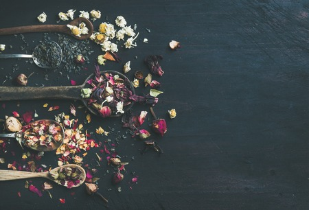 Wooden spoons with dried herbs, flower buds and tea leaves over black scorched wooden background, top view, copy space, horizontal composition