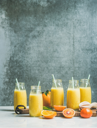 Healthy yellow smoothie with citrus fruit and ginger in bottles on wooden board over light marble table, selective focus, copy space. Clean eating, vegan, dieting, weight loss food concept Stock Photo