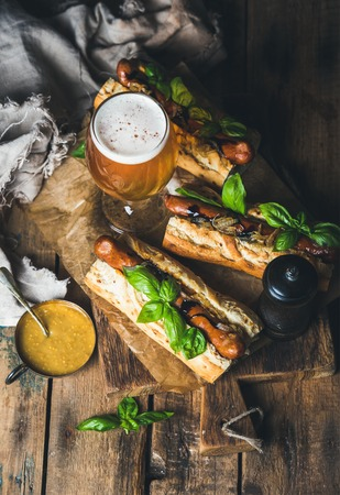 pepperbox: Glass of wheat unfiltered beer and homemade grilled sausage dogs in baguette with mustard, caramelised onion and herbs on serving board over rustic wooden background, selective focus, copy space Stock Photo
