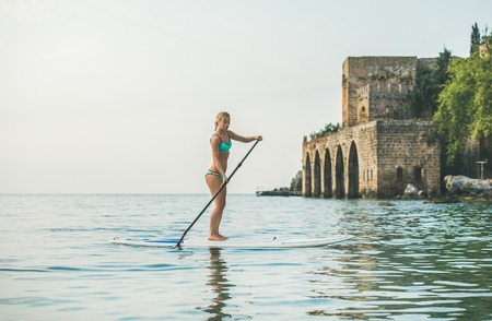 Young beautiful european woman tourist practicing paddle boarding in sea at beach near ancient fortress wall and shipyard in city center of Alanya, Mediterranean Turkey