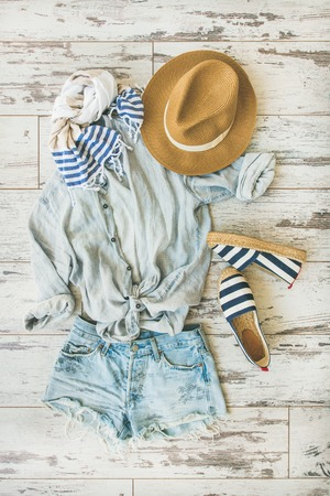 Summer outfit flatlay. Pastel coloured summer womens clothes, parquet background, top view. Blue shorts, linen shirt, straw hat, yellow bag, sunglasses, striped neckerchief, espadrillas