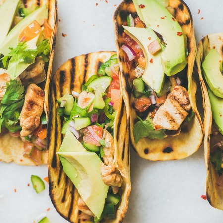 stuffing: Healthy corn tortillas with grilled chicken fillet, avocado, fresh salsa, limes over light grey marble table background, top view, square crop. Gluten-free, allergy-friendly, weight loss concept