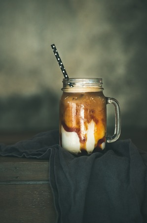 Iced caramel macciato coffee with milk in glass jar with straw on dark rustic wooden table, selective focus, copy space. Cold sweet refreshing summer drink concept Stock Photo