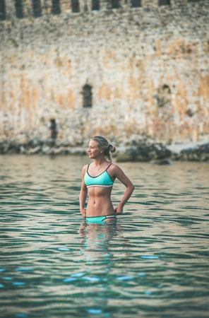 Young beautiful slavian woman tourist wearing turquoise bikini swimming at beach near ancient fortress wall and shipyard in city center of Alanya, Mediterranean Turkey