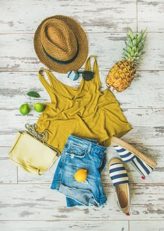 Colorful summer fashion outfit flat-lay. Denim shorts, straw sun hat, yellow top, espadrillas, leather shoulder bag, sunglasses, pineapple, limes and lemon over pastel parquet background, top view Standard-Bild