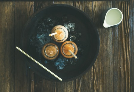 Refreshing summer drink. Cold Thai iced tea in glass bottles with milk on plate over dark wooden background, top view, copy space. Vegetarian, healthy food concept
