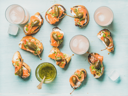 caper: Crostini with smoked salmon, pesto sauce, watercress and capers and pink grapefruit cocktails in glasses over light blue background, flat-lay, top view. Party, catering or fingerfood concept