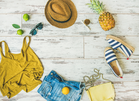 Colorful summer fashion outfit flat-lay. Denim shorts, straw sun hat, yellow top, espadrillas, leather bag, sunglasses, pineapple, limes and lemon over pastel parquet background, top view, copy space