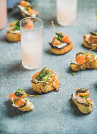 Crostini with smoked salmon, pesto sauce, watercress and capers and pink grapefruit cocktails over grey background, selective focus, copy space. Party, catering or fingerfood concept Stock Photo