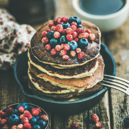 Sweet breakfast with pancakes with fresh forest berries and honey in cast iron pan over rustic wooden background, selective focus, square crop